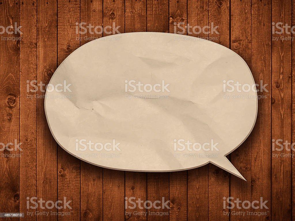 blank paper speech bubble on wood background stock photo