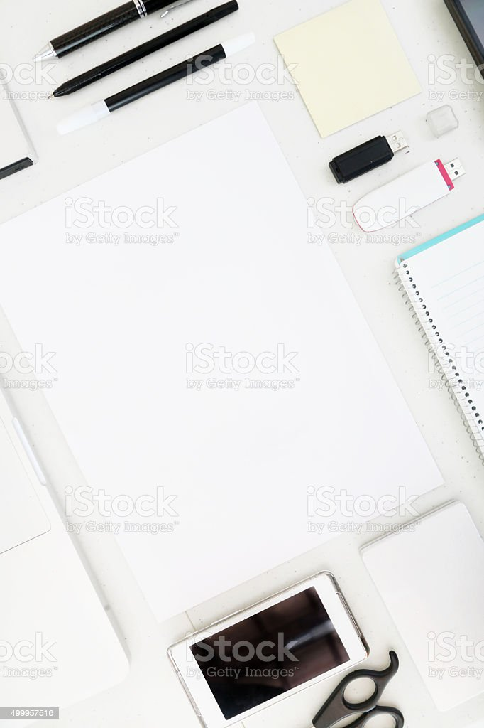 Blank paper surounded by various office items stock photo