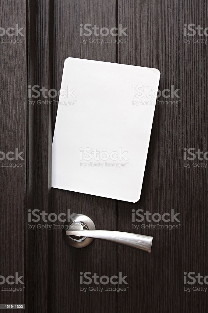 Blank paper to write  nested in gap under wooden door. royalty-free stock photo