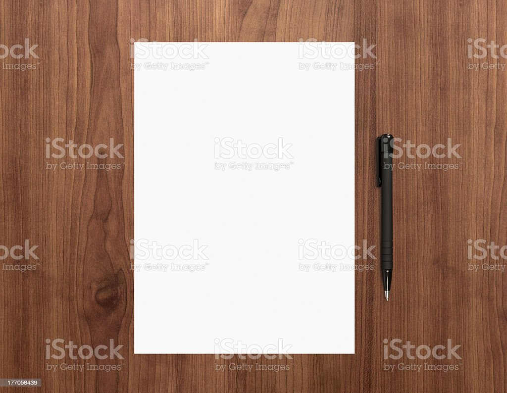 Blank paper with pen on desk stock photo