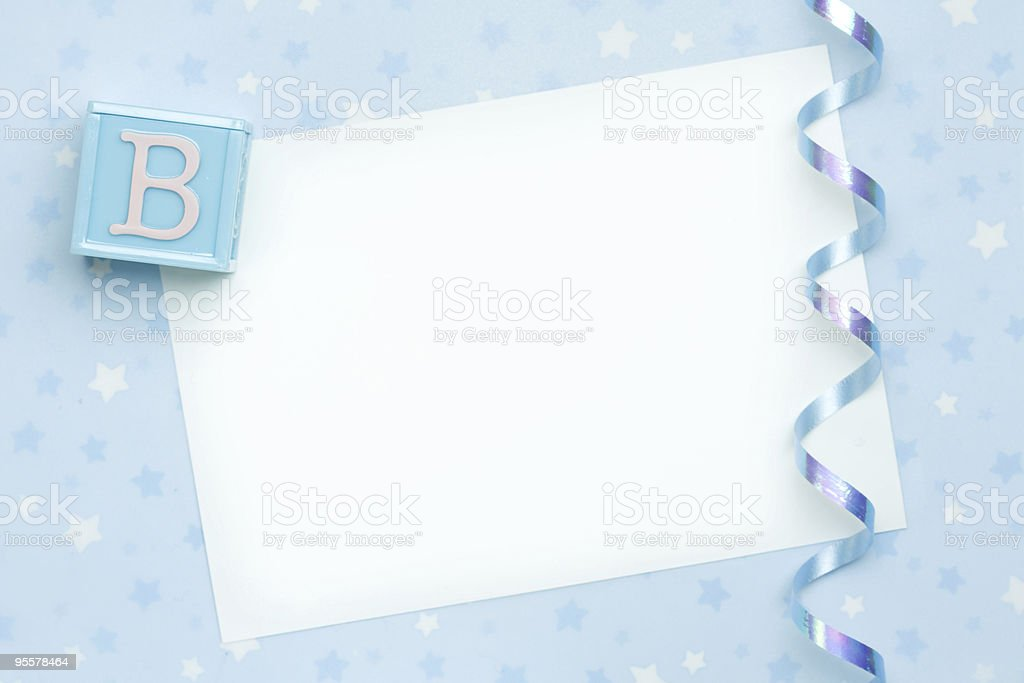 Blank paper with ribbon and blue block representing new baby stock photo
