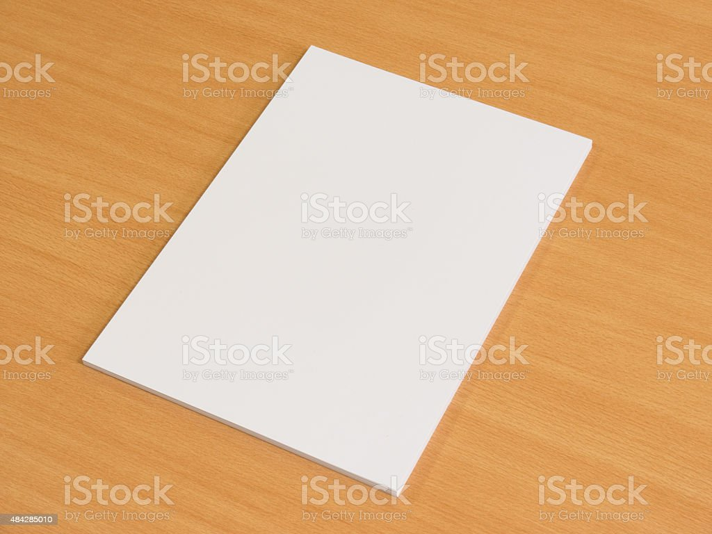 Blank papers on wooden office table stock photo