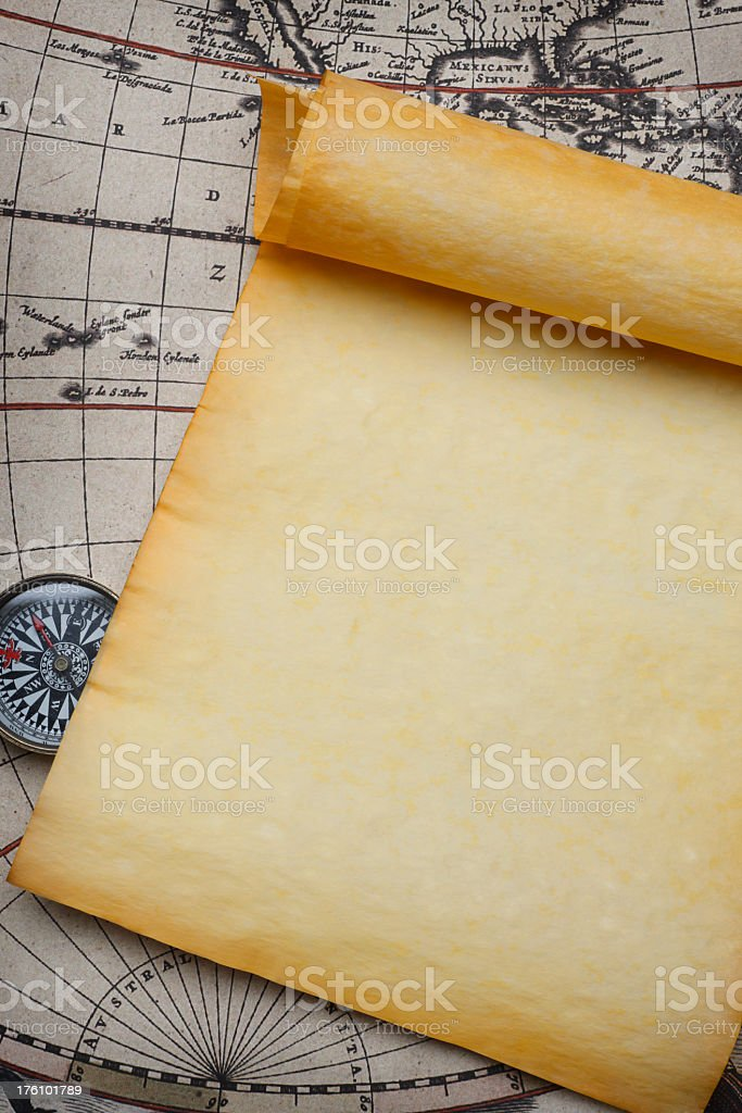 Blank Parchment Scroll And Compass On Old Map stock photo