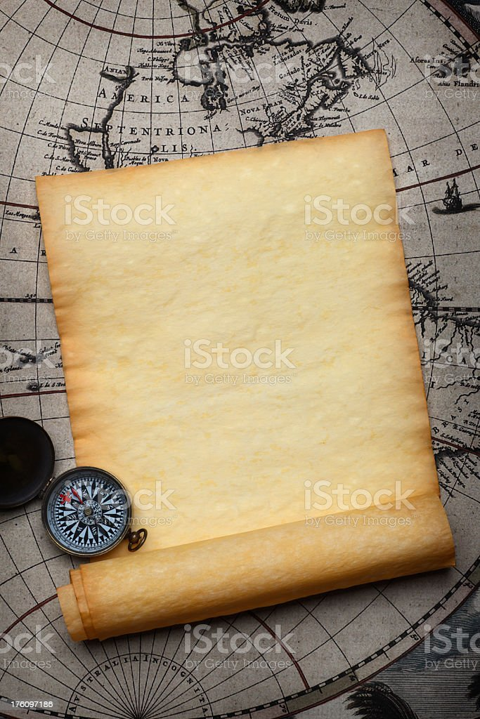 Blank Parchment Scroll And compass On Top Of Old Map stock photo