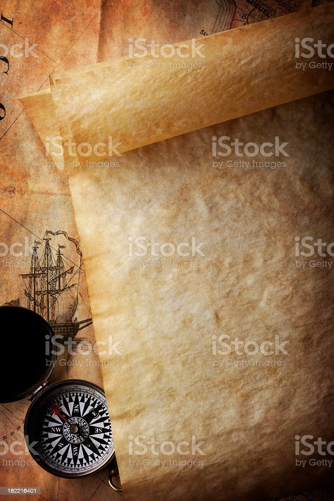 Blank Parchment Scroll With Compass On Top Of Old map stock photo
