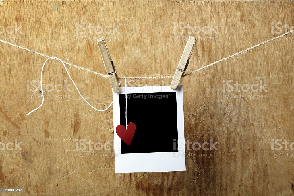 Blank picture frame and small heart hanging on clothesline royalty-free stock photo