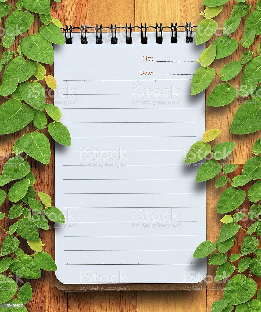 Blank planning notebook on wood background with ivy fixing tree. royalty-free stock photo