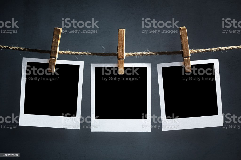Blank polaroid photographs hanging on a clothesline stock photo