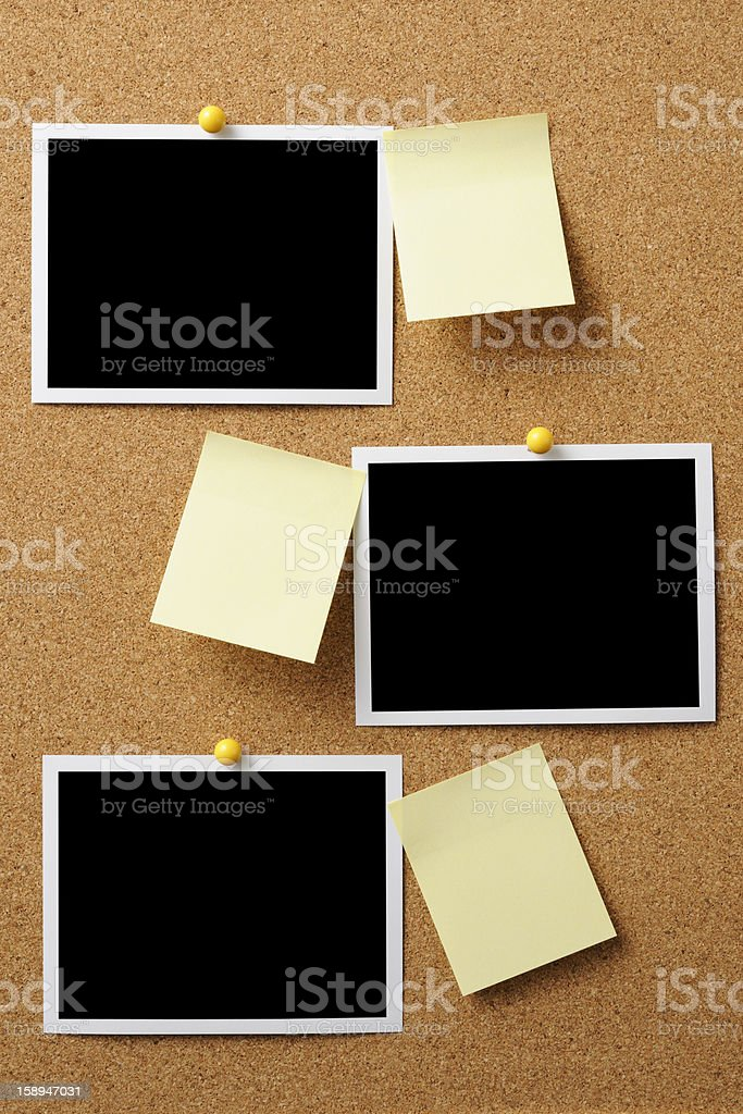 Blank Polaroid with yellow sticky note pinned on cork board stock photo
