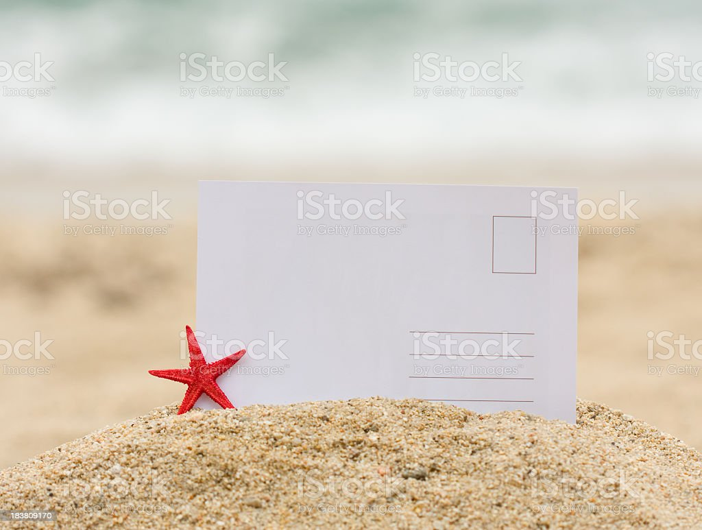 Blank postcard stuck in mound of sand next to a starfish stock photo