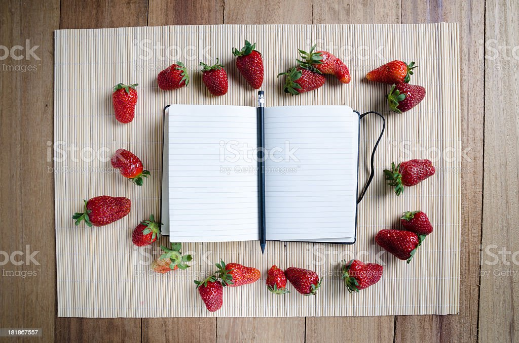 Blank recipe book surrounded by strawberries stock photo