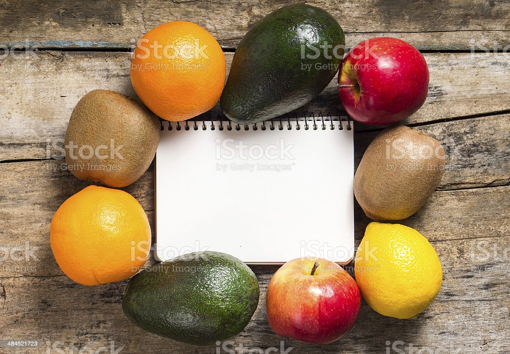 Blank Recipe Notepad with Different Fruits Around on Wood Background stock photo