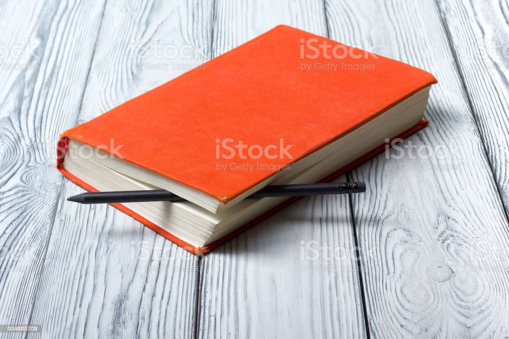 Blank red hardcover book with black pencil on white wooden stock photo