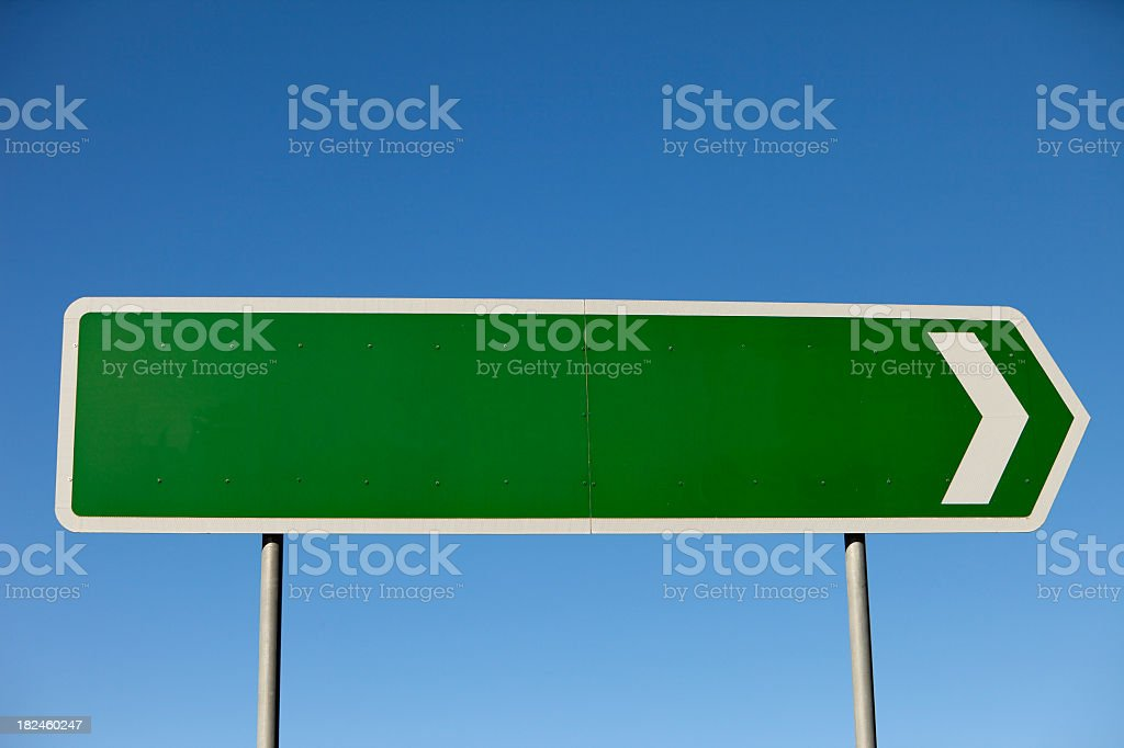 Blank road sign pointing to the right with blue sky stock photo