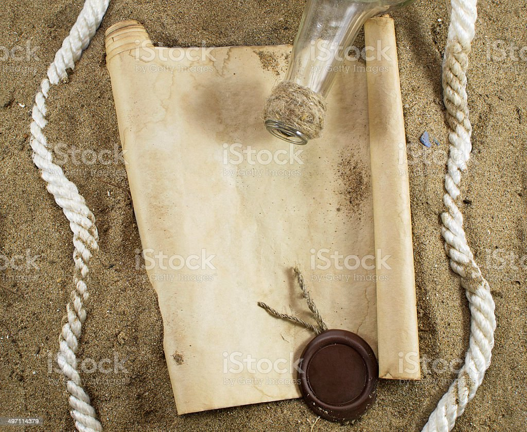 Blank rolled paper in the sand with a bottle stock photo