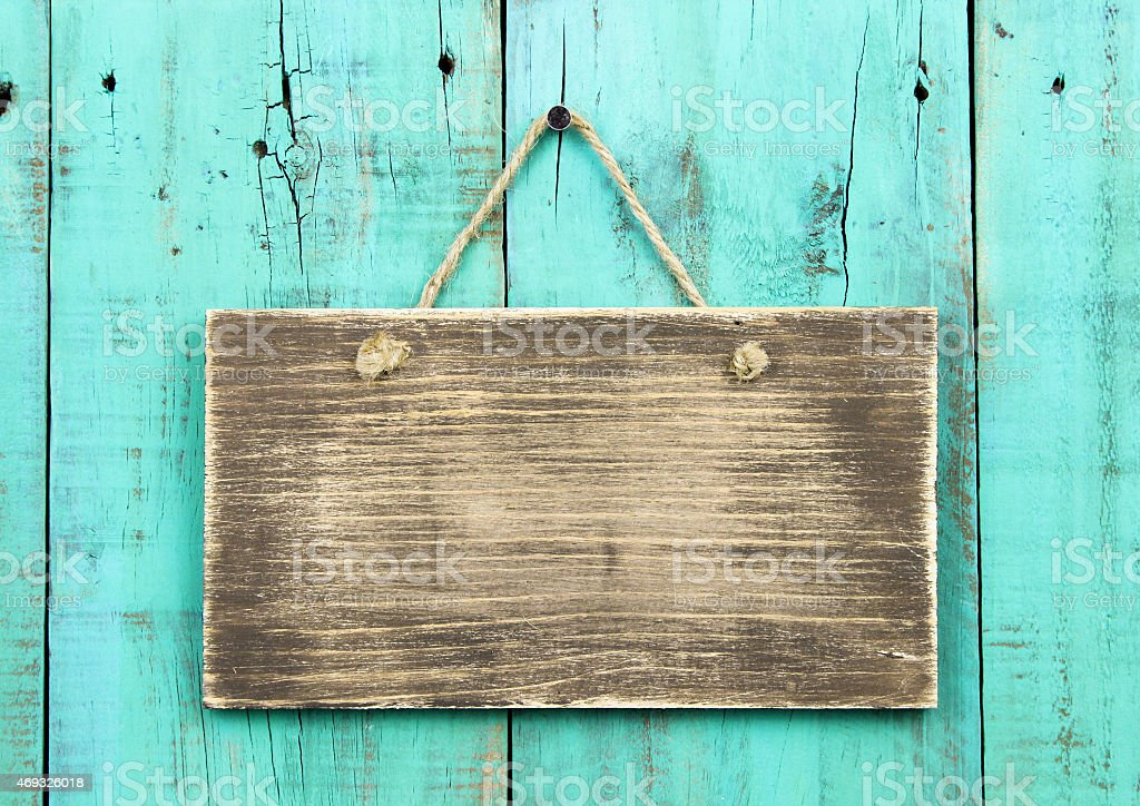 Blank rustic sign hanging on distressed wooden turquoise fence stock photo
