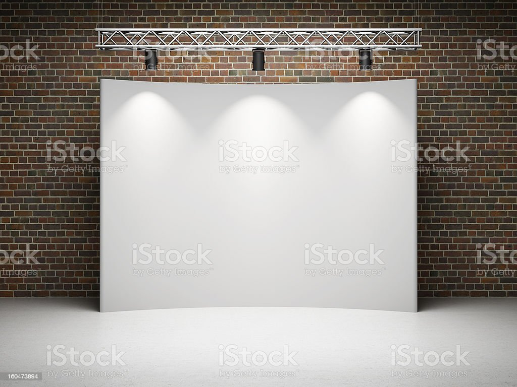 Blank screen and stage lighting above in front of brick wall stock photo
