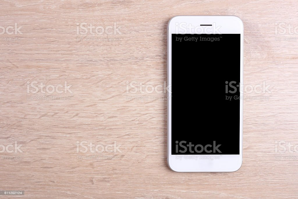 Blank screen smartphone on wooden background stock photo