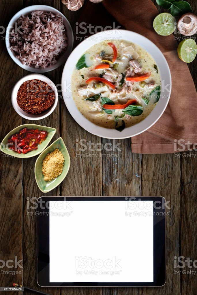 Blank screen tablet and Green Chicken Curry over wooden table.Thai cuisine stock photo