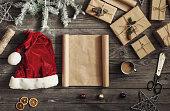 Blank sheet of paper on wooden table with christmas presents