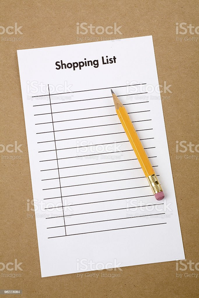 Blank shopping list and a pencil on a cardboard background royalty-free stock photo