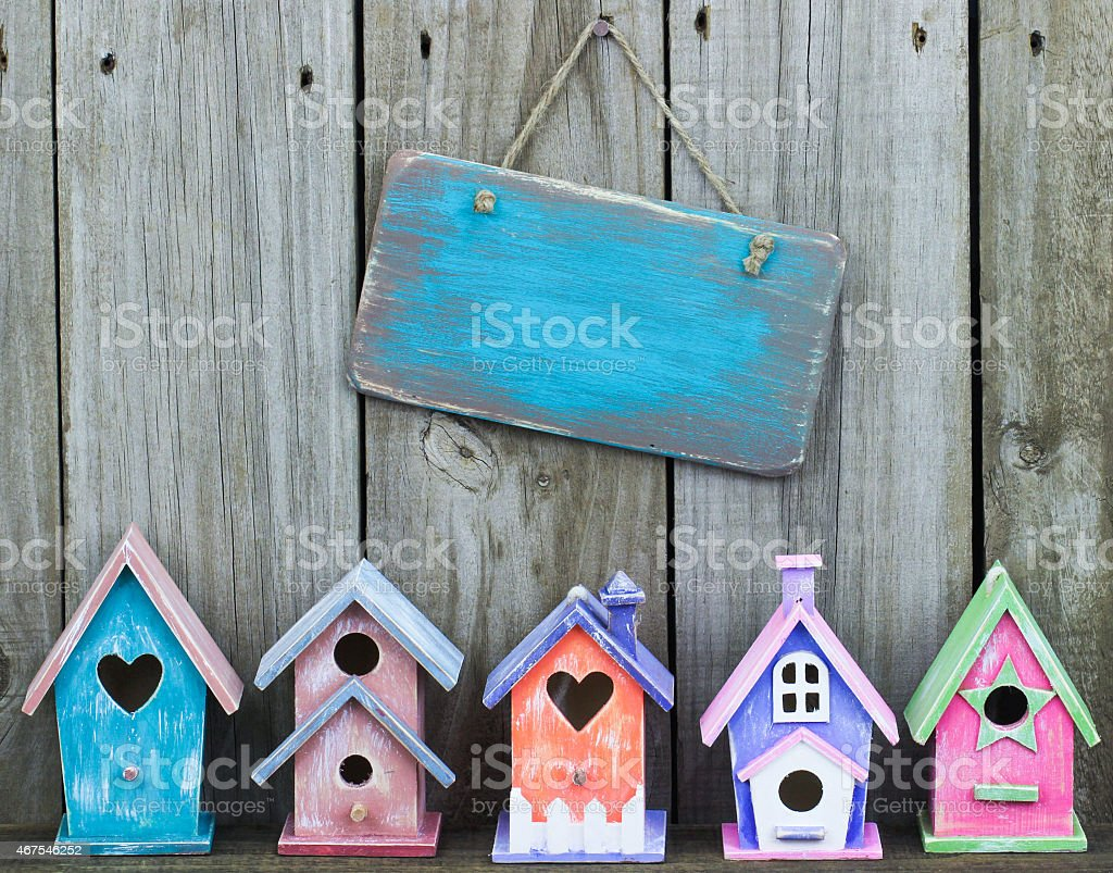 Blank sign hanging by row of colorful birdhouses stock photo