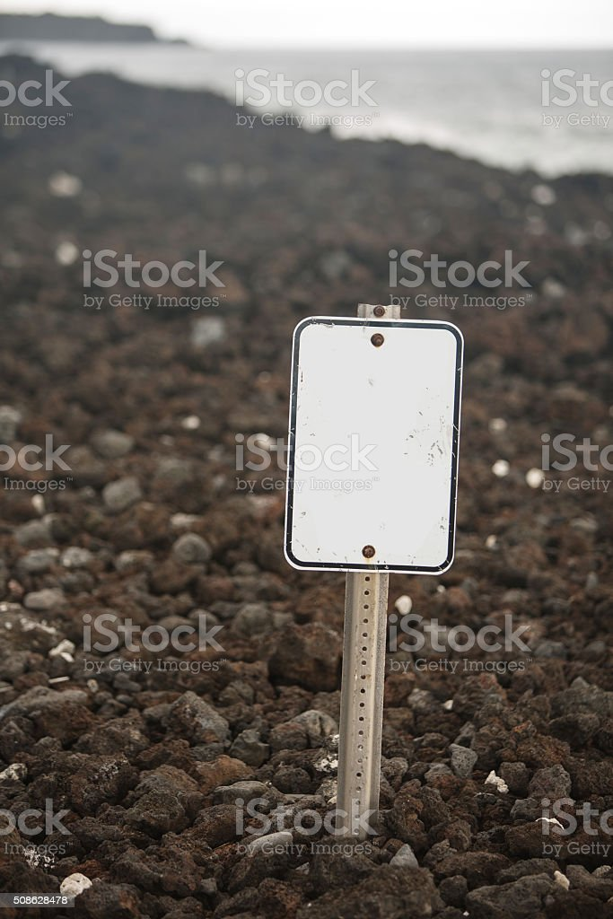 Blank Sign on Rock Beach stock photo