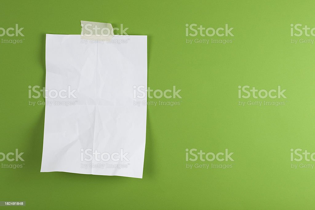 Blank sign taped on green background stock photo