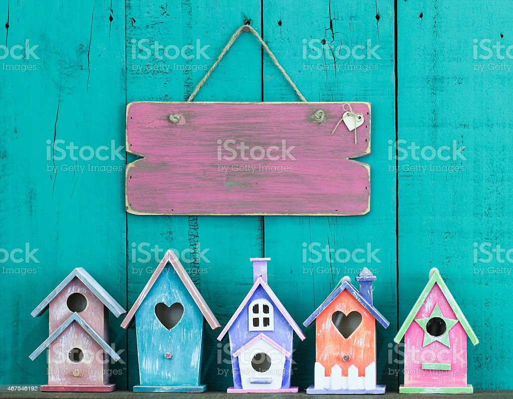 Blank sign with heart hanging by colorful birdhouses stock photo