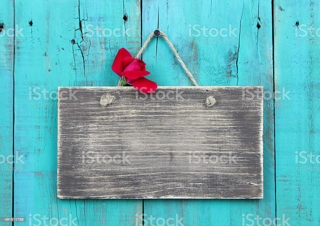 Blank sign with rose hanging on teal blue door stock photo