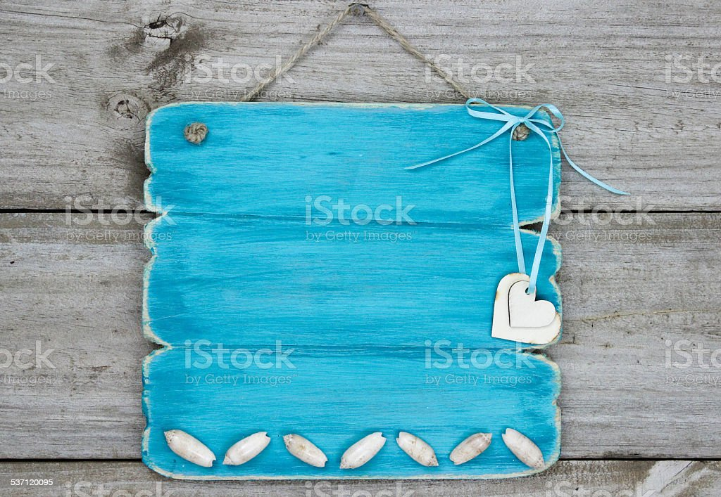 Blank sign with seashells and hearts hanging on wooden background stock photo
