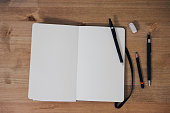 Blank sketchbook on wooden table with crayons