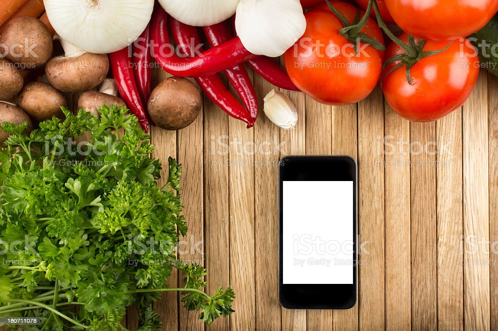 A blank smartphone on a wooden table surrounded by veggies royalty-free stock photo