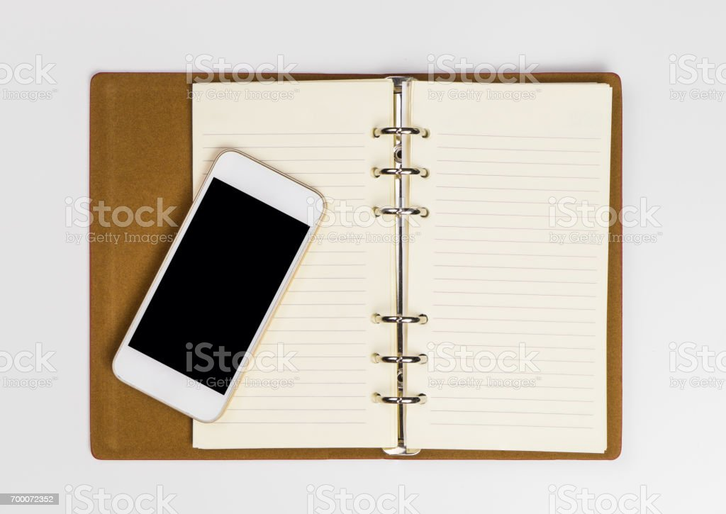Blank Smartphone on an open notebook page for diary organizer concept stock photo