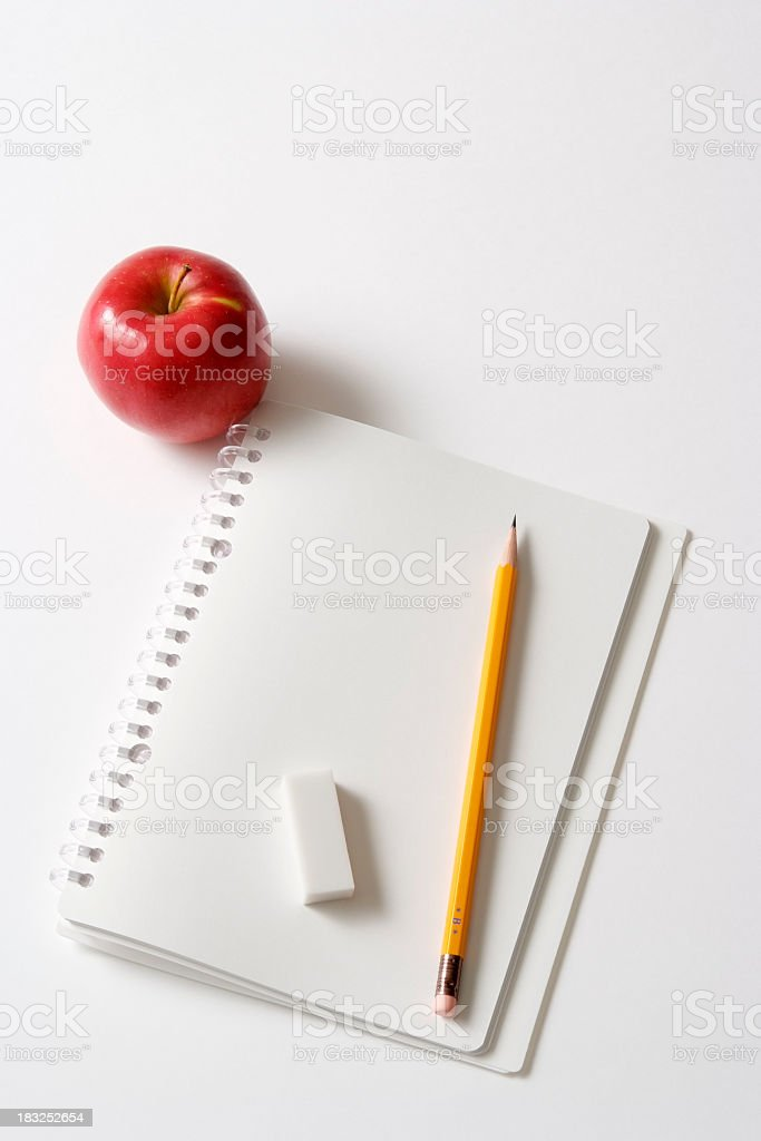 Blank spiral notebook and pencil with apple on white background royalty-free stock photo