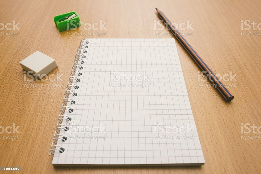 Blank squared paper notebook on wooden desk in perspective view stock photo