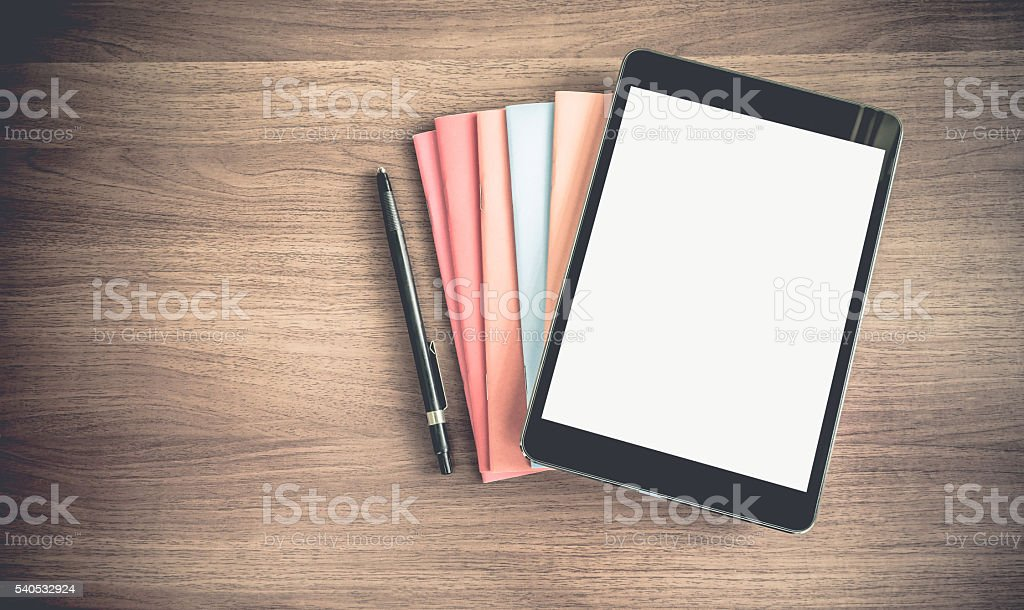 blank tablet on stack of book on table stock photo