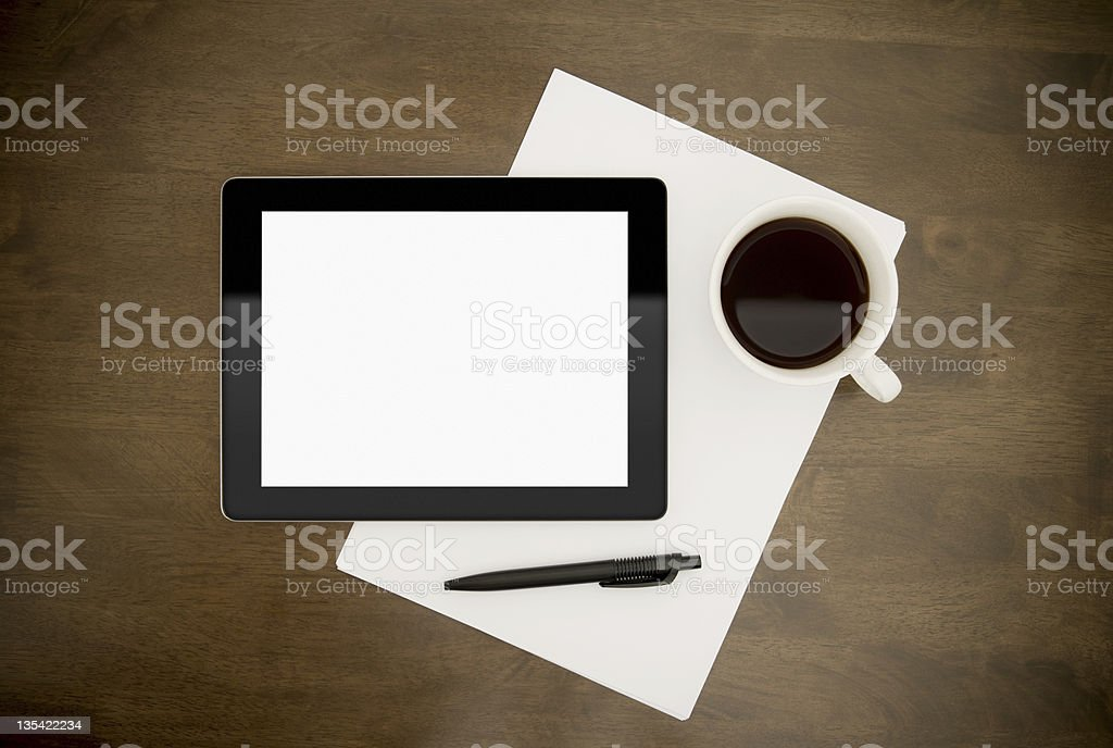 Blank tablet, paper, pen and coffee on wooden desk royalty-free stock photo