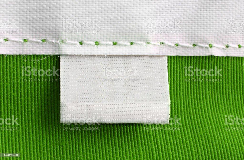A blank tag on a green handmade garment  stock photo