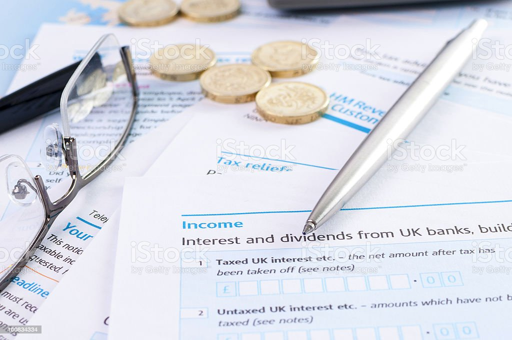 Blank UK tax form with pound coins and pen royalty-free stock photo