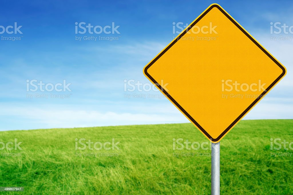 Blank Warning Sign Against Grass and Sky stock photo