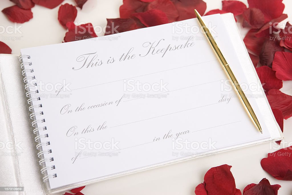 Blank Wedding Guest Book and Gold Pen with Rose Petals stock photo