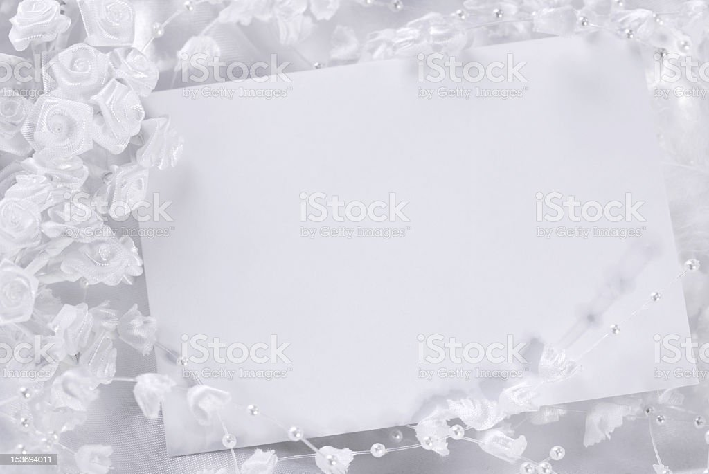 A blank wedding invitation with white flowery decorations  stock photo