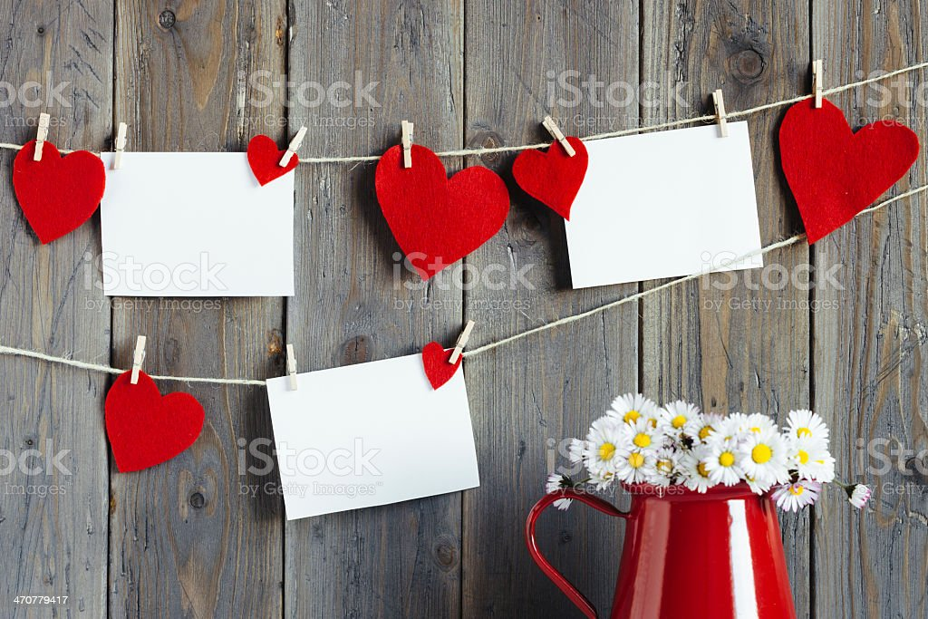 Blank white and heart red notes hanging by a wooden wall stock photo