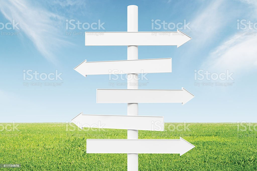 Blank white arrows-pointers at green grass and blue sky backgrou stock photo