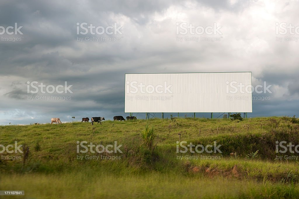 A blank white billboard in the middle of a field royalty-free stock photo