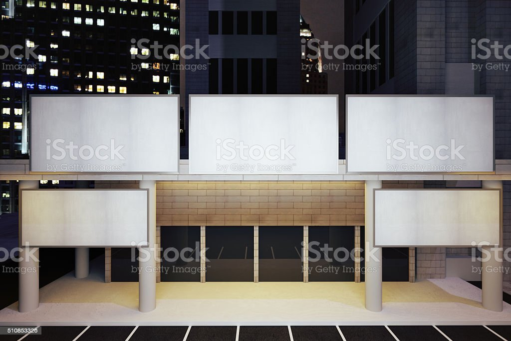 Blank white billboards on modern building in night city district stock photo