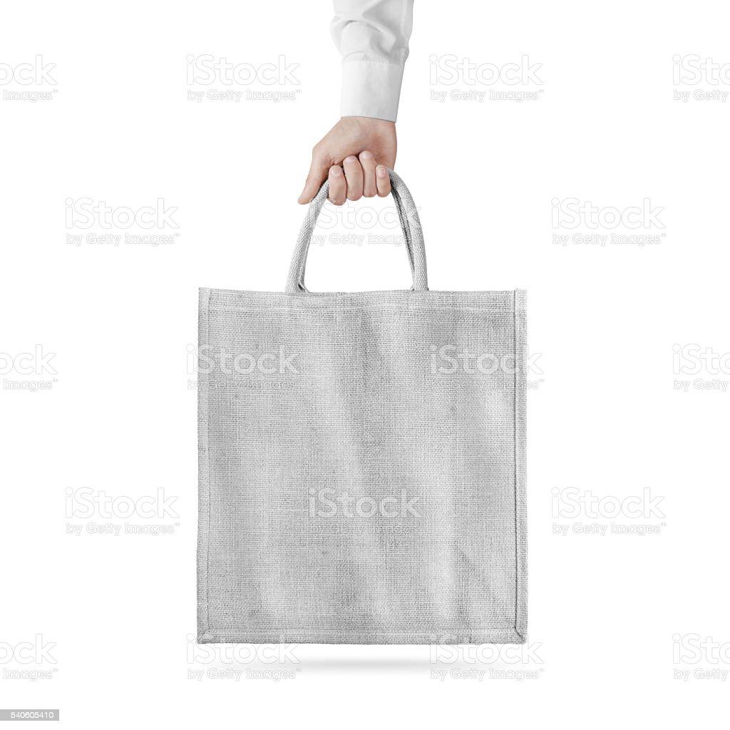 Blank white cotton eco bag design mockup isolated, holding hand stock photo