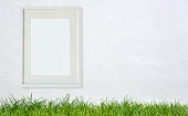 Blank white frame with green grass and White Wall Background.