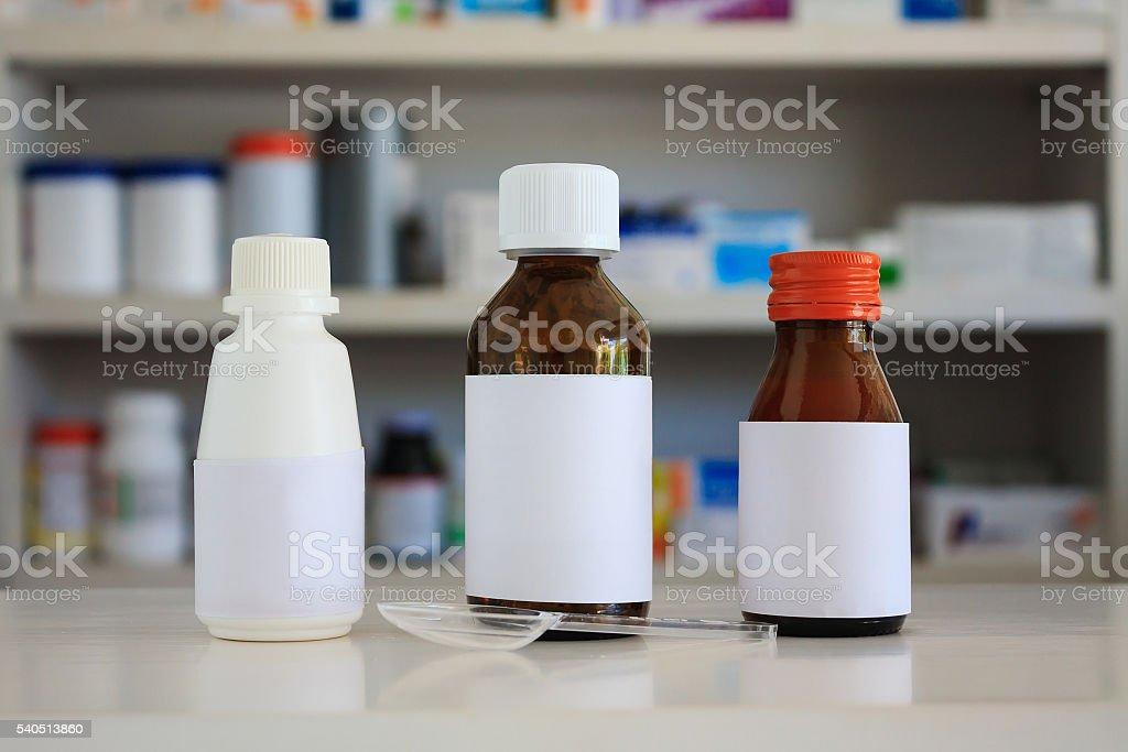 Blank white label of medicine bottle with blur pharmacy shelves stock photo